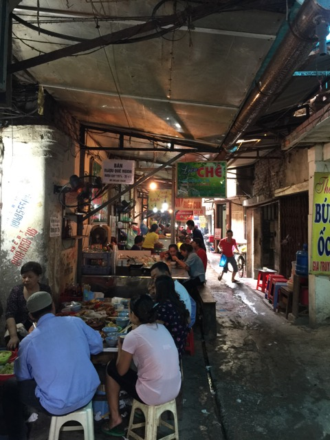 A covered alley outside Đồng Xuân Market featuring a variety of food stalls