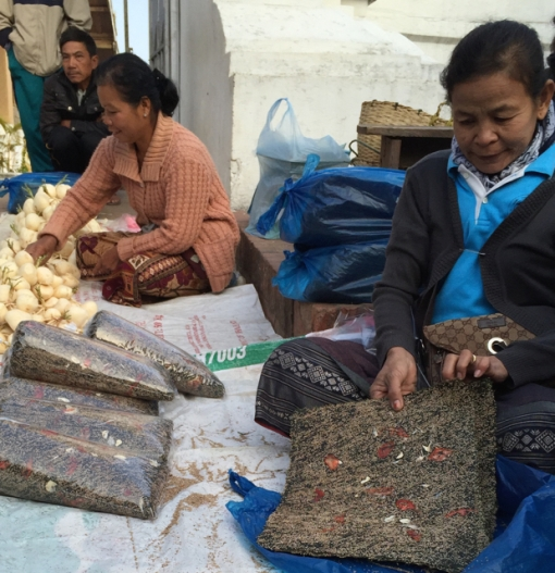 A lady selling sheets of kai phaen at the morning market