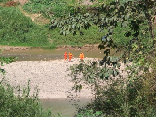 Young monks crossing the river